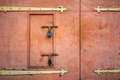Old rusted padlock hanging on gray metal retro door Royalty Free Stock Photo