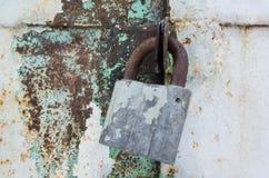 Old rusted padlock hanging on metal door Stock Image