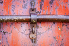 Old rusted padlock on red metal door Stock Photo
