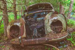 Old rusted scrap car in a forest. Retro styled image of an old rusted and weathered scrap car in a forest Stock Images