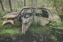 Old rusted scrap car in a forest. Old rusted and weathered scrap car in a forest stock photo