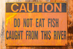 Old Rusted Sign Reading: Caution Do Not Eat Fish Caught from thi Royalty Free Stock Images