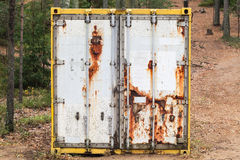 Old rusted standard cargo container. Abandoned old rusted standard cargo container stands in the forest, door face, selective focus Stock Image