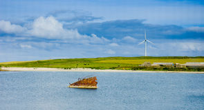 Old rusted sunken boat  and eolic fan in background. In Orkney island, Scapa Flow, Scotland Royalty Free Stock Photography