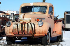 Old, Rusted Truck. An inoperable, rusted, old truck rests in a gravel and snow parking spot Royalty Free Stock Photo