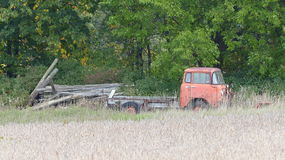 Old, Rusted Truck. This old rusted truck sits alone near a tree line and in front of a field stock image