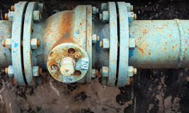Old rusted valve on industrial pipeline. Old rusted valve on blue industrial pipeline Stock Photo