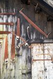 Old rusted vintage saw and tools hanging on a barn. Many old rusted vintage saw and tools hanging on a barn royalty free stock photography