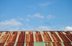 Old rusted and weathered steel quonset hut roof against a blue sky with fluff clouds Royalty Free Stock Photos