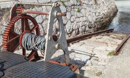 Old rusted winch, gangway in small port Stock Image