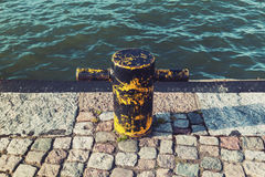 Old rusted yellow mooring bollard on stone pier Stock Images
