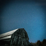 Old rustic barn with Big Dipper and Pole star in winter. Image of a moonlit antique rural Ontario barn, with the starry sky and trees behind.  The constellation Royalty Free Stock Image
