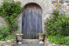 Old Rustic Barn Doorway in Brittany France. Old rustic barn doorway weathered, worn and decorated with plants in Brittany France royalty free stock photography