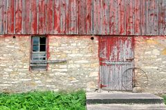 Old Rustic Barn Exterior Wall Background. The exterior wall including a broken window and barnwood door with wagon wheel of an old abandoned historic bank barn Stock Photos
