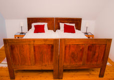Old rustic bed in modern apartment Royalty Free Stock Image