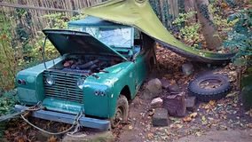 Old rustic blue car in the wilderness stock image