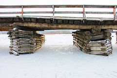 Old rustic bridge over the frozen river - photo taken in the winter Royalty Free Stock Images