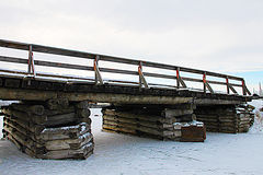 Old rustic bridge over the frozen river - photo taken in the winter Royalty Free Stock Photos
