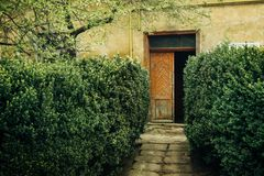 Old rustic building with wooden doors and geen garden, italian p Royalty Free Stock Photos