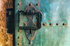 Old rustic copper castle metal door with large knocker. Old rustic copper metal castle door with large knocker, weathered surface texture royalty free stock images