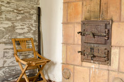 Old rustic furnace doors and wooden rest chair Royalty Free Stock Photos
