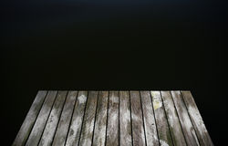 Old rustic grunge pier bridge on a dark black blue water lake wi. Th a sky reflection and ripples royalty free stock images