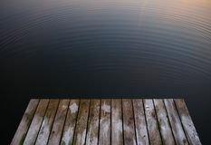Old rustic grunge pier bridge on a dark black blue water lake wi. Th a sky reflection and ripples stock photos
