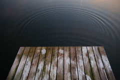 Old rustic grunge pier bridge on a dark black blue water lake wi. Th a sky reflection and ripples stock images