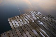 Old rustic grunge pier bridge on a dark black blue water lake wi. Th a sky reflection and ripples royalty free stock image