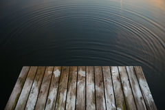 Old rustic grunge pier bridge on a dark black blue water lake wi. Th a sky reflection and ripples royalty free stock photography