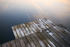 Old rustic grunge pier bridge on a dark black blue water lake wi. Th a sky reflection and ripples royalty free stock photo