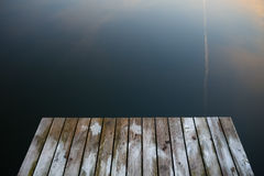 Old rustic grunge pier bridge on a dark black blue water lake wi. Th a sky reflection and ripples stock image