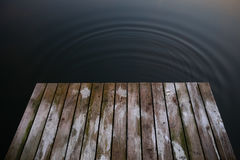 Old rustic grunge pier bridge on a dark black blue water lake wi Royalty Free Stock Photography