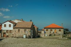 Old rustic houses made of stone in front of square. Old rustic houses made of stone in front of cobblestone square, in a sunny day at Linhares da Beira. A stock image