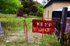 Old rustic keep out sign on metal gate stock image
