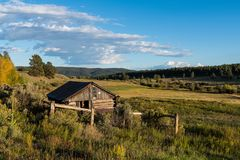 Old rustic log cabin overlooking a landscape of ranchland, fields, forest, and hills in the American West stock photo