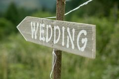 Old rustic sign pointing to a wedding. Old rustic looking hand painted wedding sign that is pointing in a direction toward a wedding Royalty Free Stock Photos