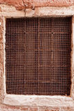 Old rustic mesh window screen on the wall Stock Photo