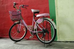 Old rustic pink bicycle. Stock Photo
