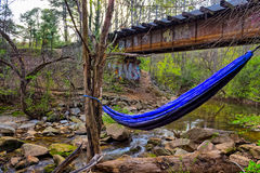 Old rustic rail road bridge with hammock and river Stock Image