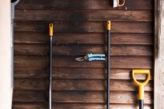 Old rustic shed with garden tools, dark wooden wall. In a winter day Royalty Free Stock Images