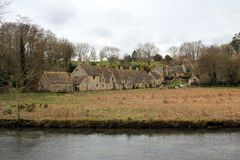 Old stone houses in english countryside and river Stock Photos
