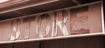 Old rustic store sign hanging, letters eroding and rusted Stock Image