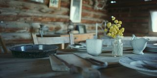 Old rustic table with dishes and utensils royalty free stock photography