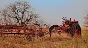 An old rustic tractor  in a field attached to a plow. A rustic tractor with a plow in a field in country Royalty Free Stock Photos