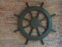 Old rustic vintage iron ship wheel over brick background. Old rustic vintage iron ship wheel, showing control, command, direction, and charge, on brick Royalty Free Stock Photo