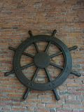 Old rustic vintage iron ship wheel over brick background. Old rustic vintage iron ship wheel, showing control, command, direction, and charge, on brick Royalty Free Stock Photos