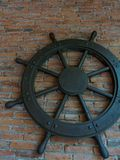 Old rustic vintage iron ship wheel over brick background. Old rustic vintage iron ship wheel, showing control, command, direction, and charge, on brick Royalty Free Stock Image