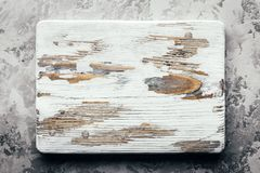Old rustic white wood board on grunge concrete table. Old rustic white wood board on rustic concrete table. Food photography stock image