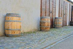 Old rustic wine barrels in front of modern wine cellar. Wine background in Europe. Czech Republic, South Moravia.  stock photography